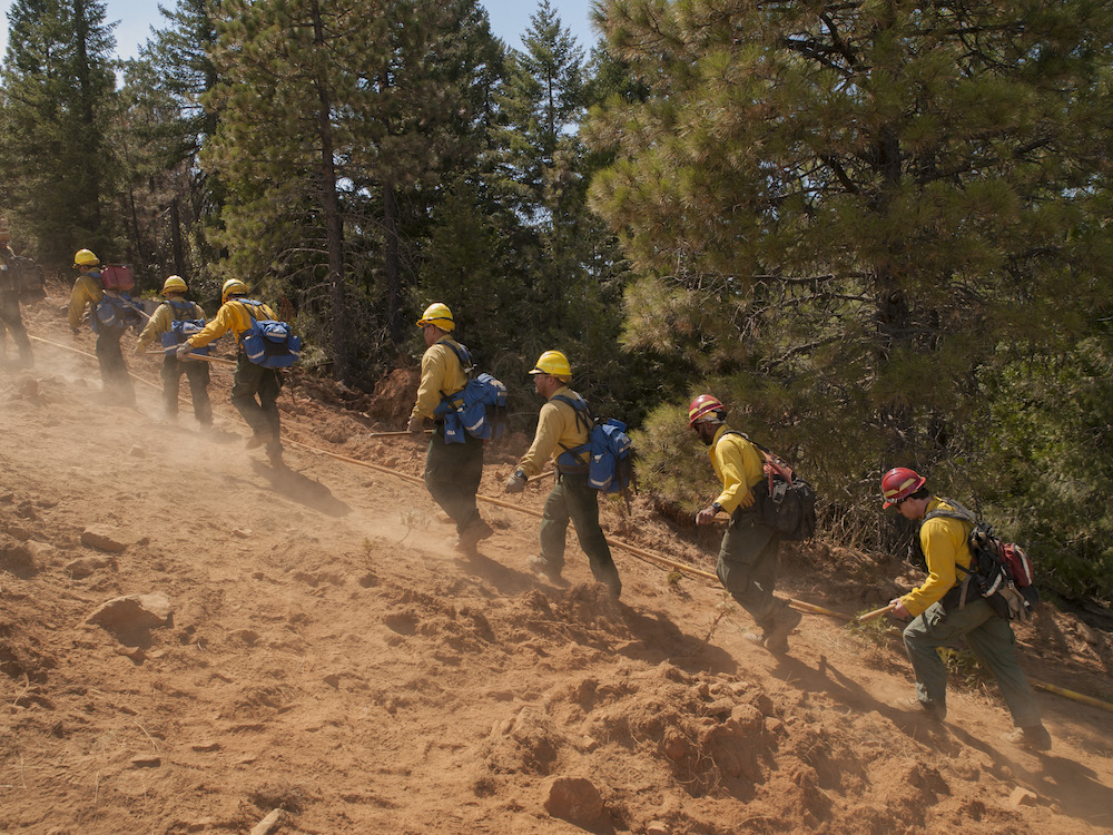 A hand crew hikes up the fireline.